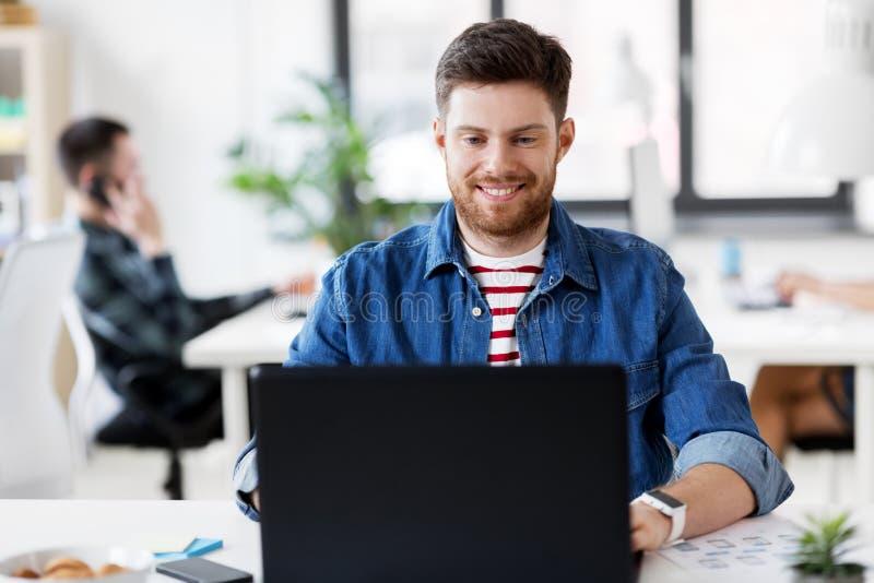 Le den idérika mannen med bärbara datorn som arbetar på kontoret royaltyfri fotografi