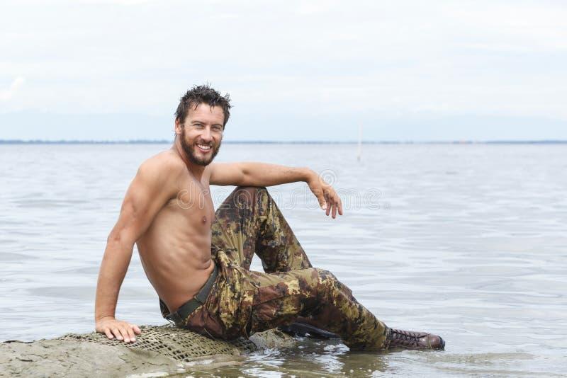 Le den idrotts- armén med ingen skjorta som poserar på stranden arkivbilder