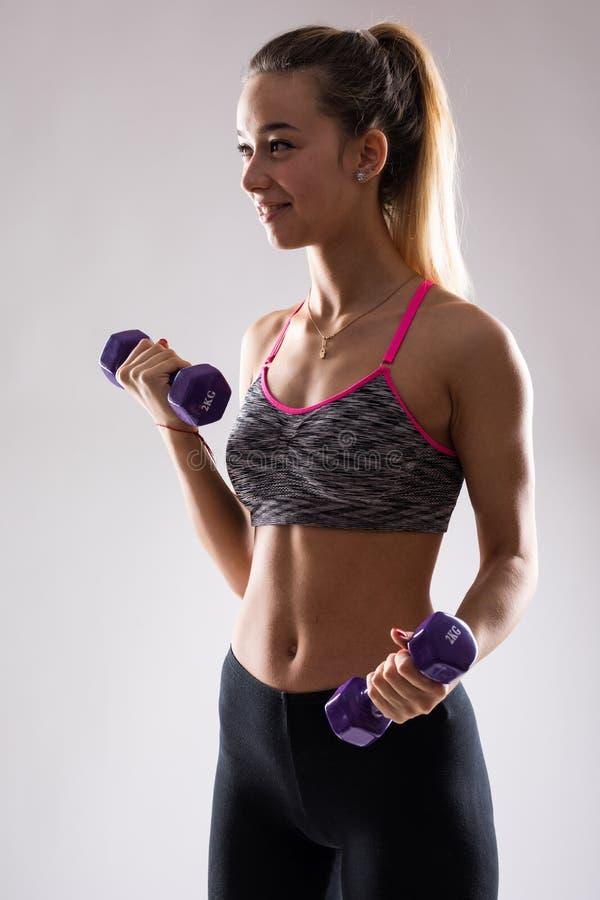 Le den idrotts- kvinnan som pumpar upp, tränga sig in med hantlar på grå bakgrund royaltyfri bild