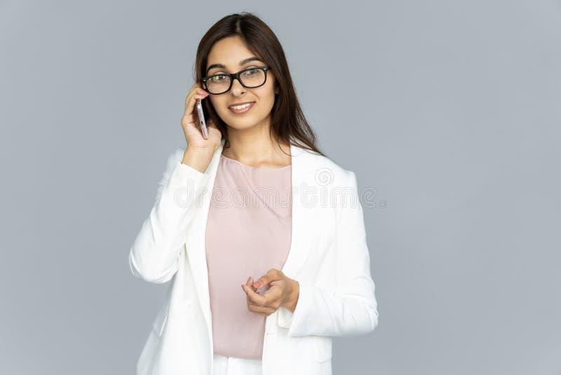 Le den indiska unga affärskvinnan som talar på telefonen som isoleras på bakgrund royaltyfri fotografi