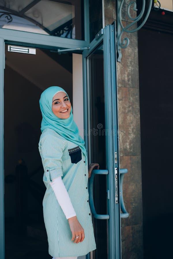 Le den islamiska flickan i öppen hotelldörr för hijab royaltyfri foto