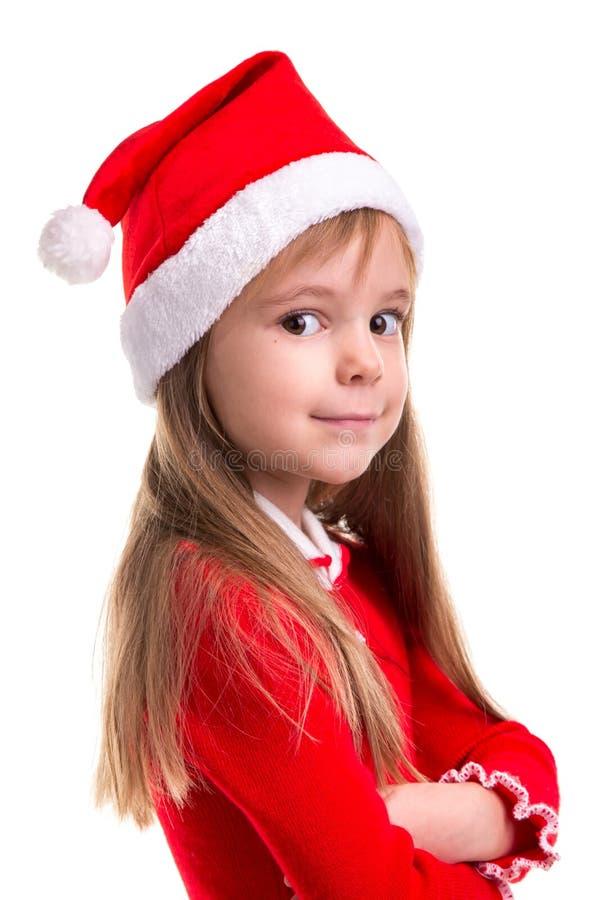 Le den kokedda julflickan som bär en santa hatt som isoleras över en vit bakgrund som står i den halva vänden royaltyfri foto