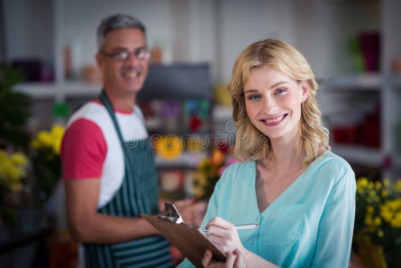 Le den kvinnliga blomsterhandlaren som noterar på skrivplattan på blomsterhandeln arkivfoton