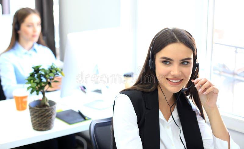Le den kvinnliga call centeroperatören som gör hennes jobb med en hörlurar med mikrofon, medan se kameran arkivfoto
