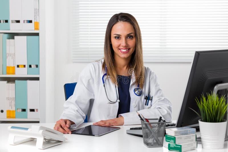 Le den kvinnliga doktorn på skrivbordet genom att använda minnestavlan royaltyfri fotografi