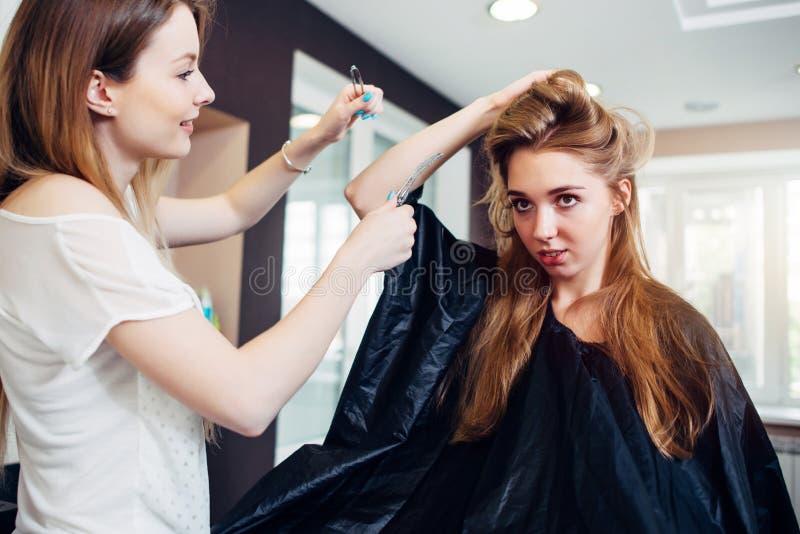 Le den kvinnliga frisören som gör frisyr till den nätta unga kvinnan med långt ganska hår i friseringsalong royaltyfri bild