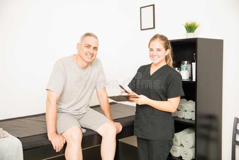 Le den kvinnliga fysioterapeutHolding Clipboard By patienten på H royaltyfria foton
