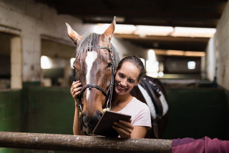 Le den kvinnliga jockeyn som använder den digitala minnestavlan, medan stå vid hästen arkivfoton