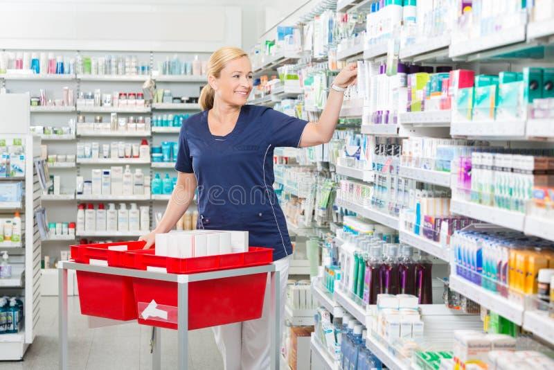Le den kvinnliga kemisten Arranging Products In fotografering för bildbyråer