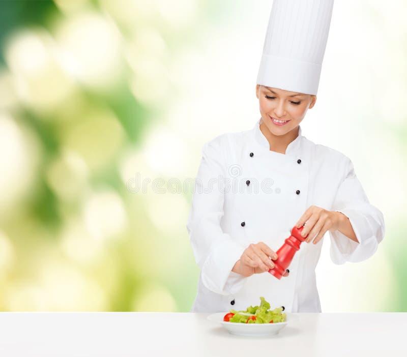 Le den kvinnliga kocken med att förbereda sallad royaltyfri fotografi