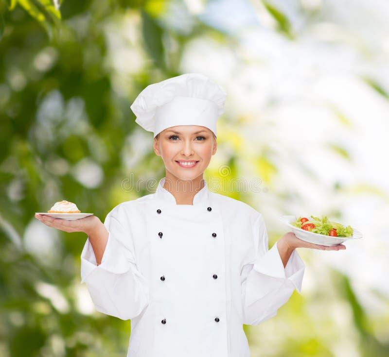 Le den kvinnliga kocken med sallad och kakan på plattor royaltyfri fotografi