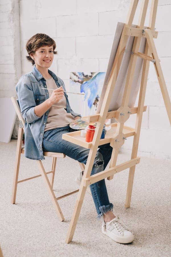 Le den kvinnliga konstnären vid staffli arkivbilder