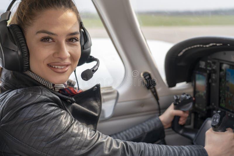 Le den kvinnliga piloten i cockpiten av ett flygplan royaltyfri foto