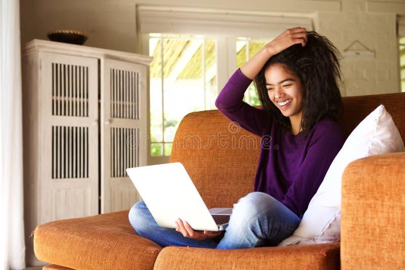le den kvinnliga studenten som sitter hemmastatt arbete på bärbara datorn royaltyfria foton