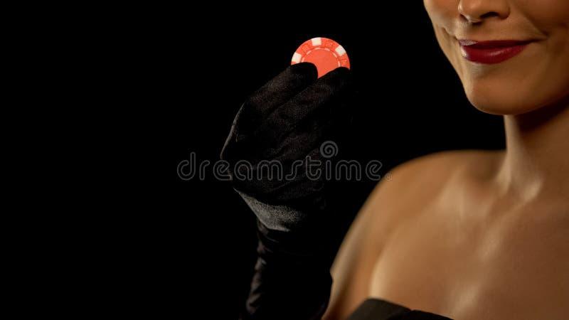 Le den kvinnliga visningdobblerichipen in i kameran som isoleras p? svart bakgrund royaltyfri bild