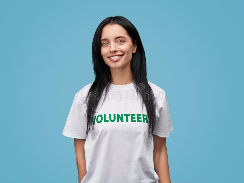 Le den kvinnliga volontären som ser kameran royaltyfri bild