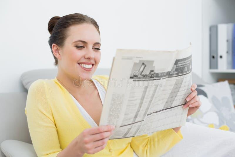 Le den läs- tidningen för kvinna på soffan hemma arkivfoton