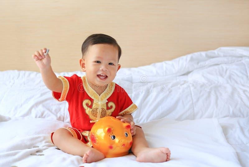 Le den lilla asiatet behandla som ett barn pojken i den traditionella kinesiska kl?nningen som s?tter n?gra mynt in i en spargris arkivfoto
