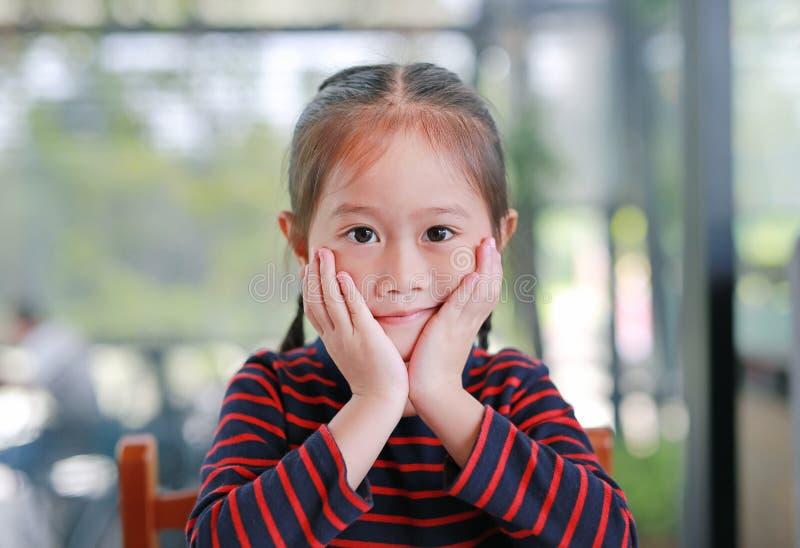 Le den lilla asiatiska barnflickan med att trycka på hennes kind som ser rak på kameran som sitter i kafét arkivfoto