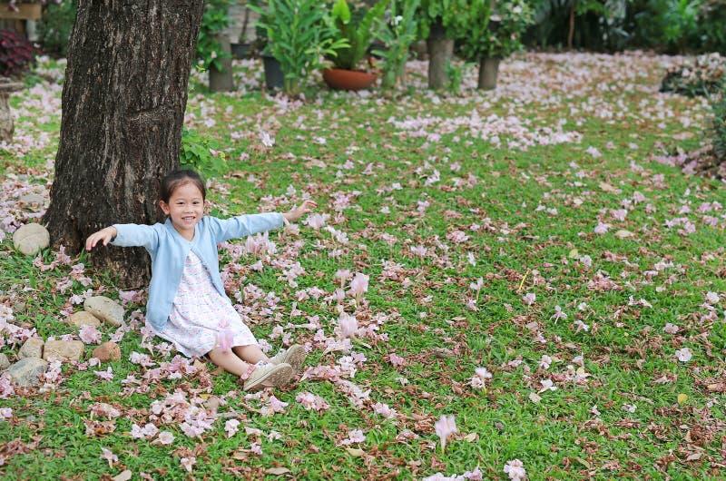 Le den lilla asiatiska barnflickan som sitter på grönt gräs under trädstammen med den fallande rosa blomman i, parkera trädgården royaltyfria foton
