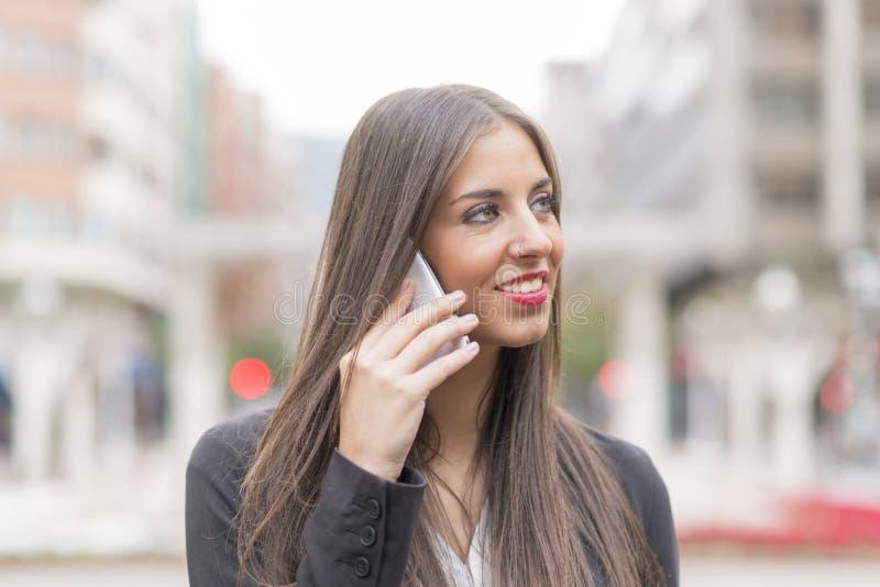Le den lyckade affärskvinnan som talar vid telefonen i gatan royaltyfri bild