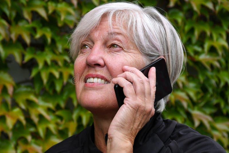 Le den lyckliga äldre kvinnan som talar utanför på en mobiltelefon med trevliga höstsidor arkivfoton