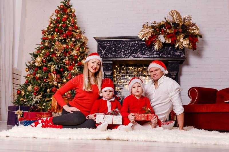 Le den lyckliga familjen i jultomten röda lock som sitter nära julgranen fotografering för bildbyråer