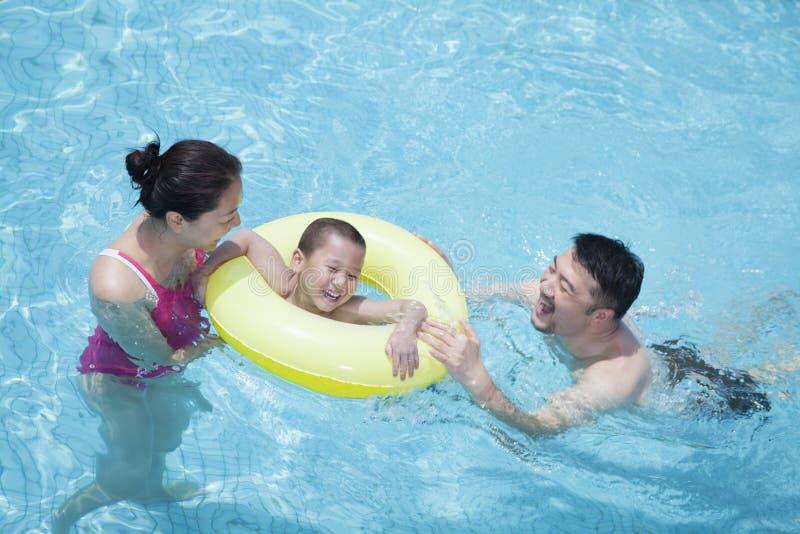 Le den lyckliga familjen som spelar i pölen med deras son i ett uppblåsbart rör royaltyfri bild