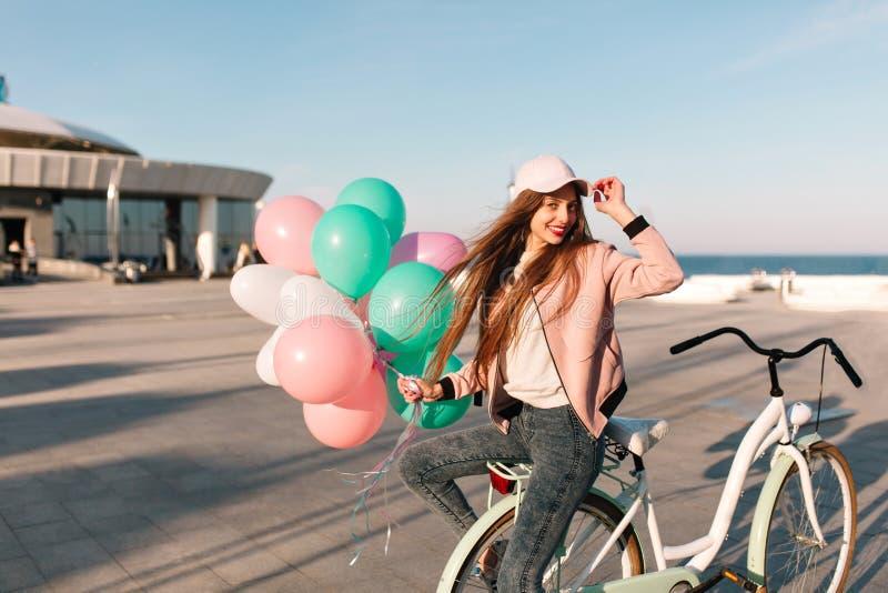 Le den lyckliga flickan med väntande vänner för långt hår på havspir för en gemensam cykelritt i morgon St?ende av gladlynt royaltyfri bild