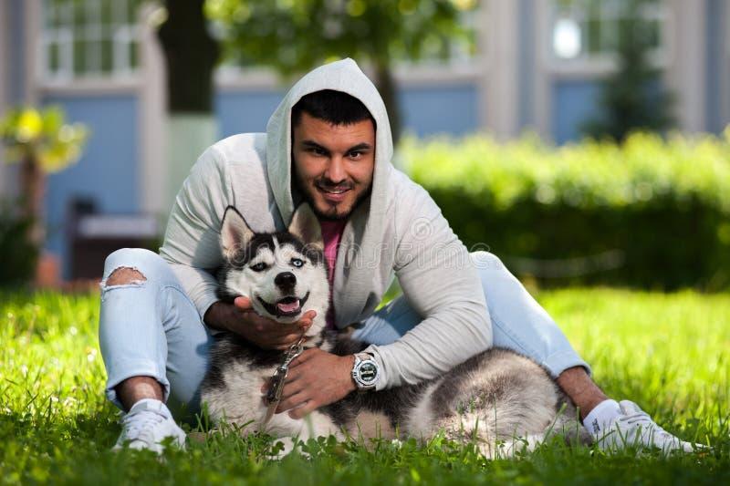Le den lyckliga grabben med hans skrovliga hund parkera in royaltyfri foto