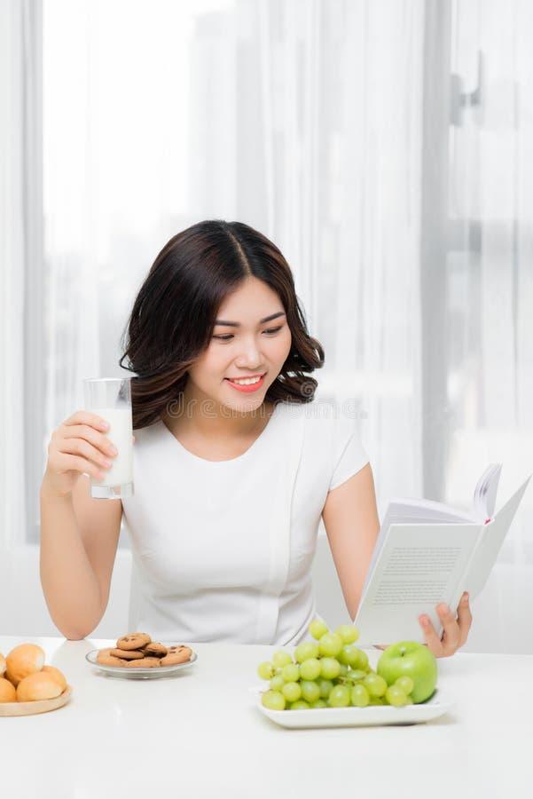 Le den lyckliga kvinnan som har en avslappnande sund frukost hemma royaltyfri bild