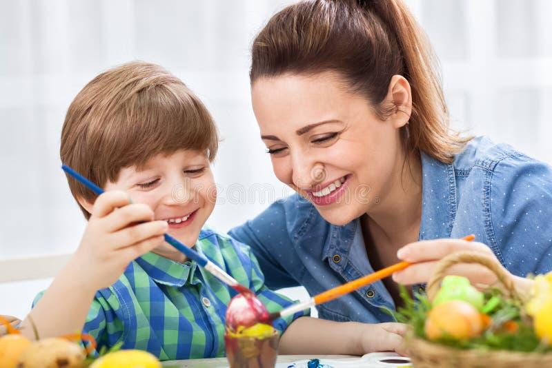 Le den lyckliga modern och barnet tyck om, i att måla easter ägg arkivbilder