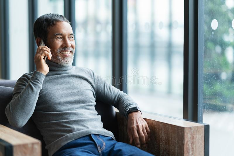 Le den lyckliga mogna asiatiska mannen med det vita stilfulla korta skägget genom att använda smartphoneminnestavlan som talar på royaltyfria bilder