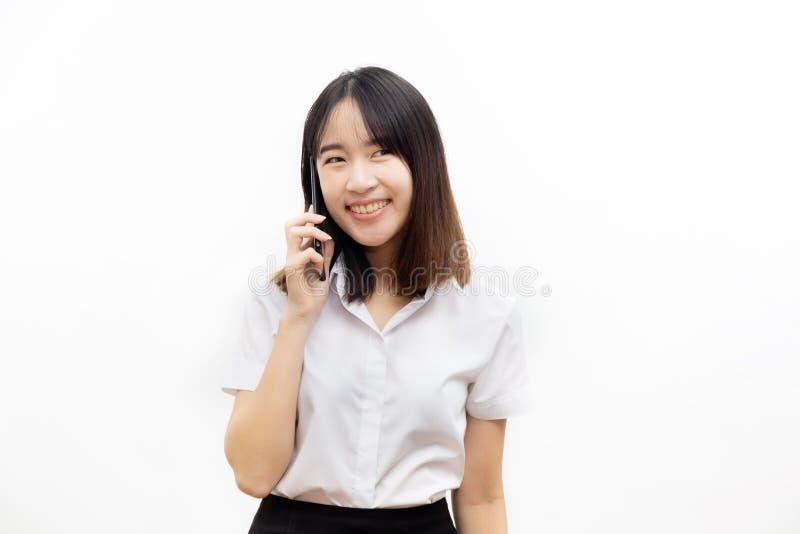 Le den lyckliga och gladlynta asiatiska kvinnliga formella klänningen som rymmer en smart mobiltelefon som gör en påringning isol arkivbilder