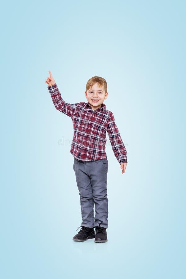 Le den lyckliga pojken som pekar upp fingret på copyspace royaltyfria bilder