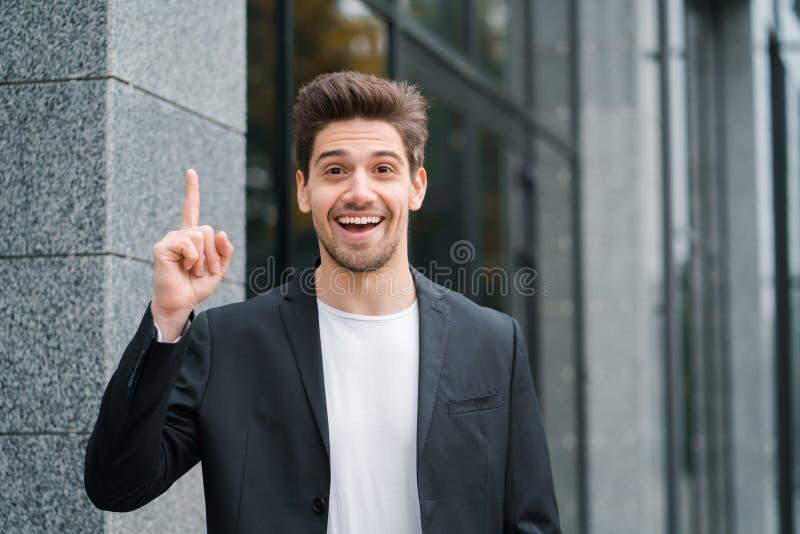 Le den lyckliga studentmannen som visar den eureka gesten Stående av den unga tänkande grubbla affärsmannen som har idéögonblick arkivbilder