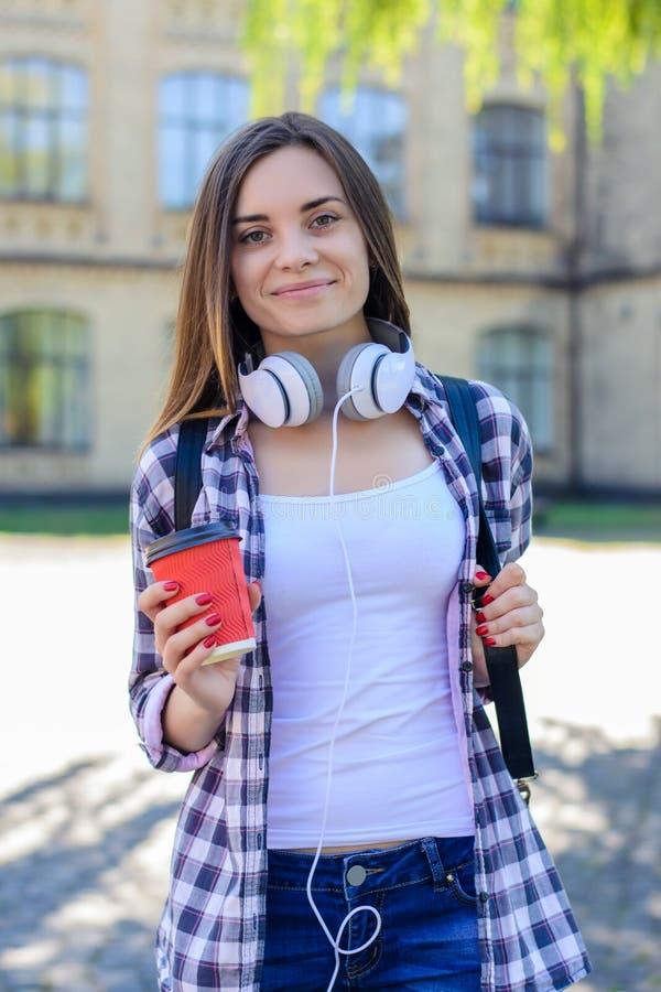Le den lyckliga unga flickan i jeans och rutig skjorta med backp royaltyfri foto