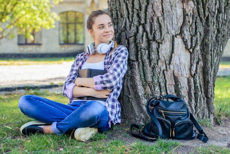 Le den lyckliga unga kvinnan i rutig skjorta och jeans som sitter nolla arkivbild