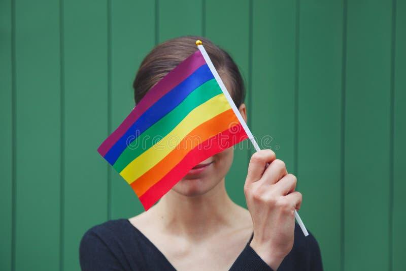 Le den lyckliga unga kvinnan som rymmer den färgrika regnbågeflaggan för lgbt fotografering för bildbyråer