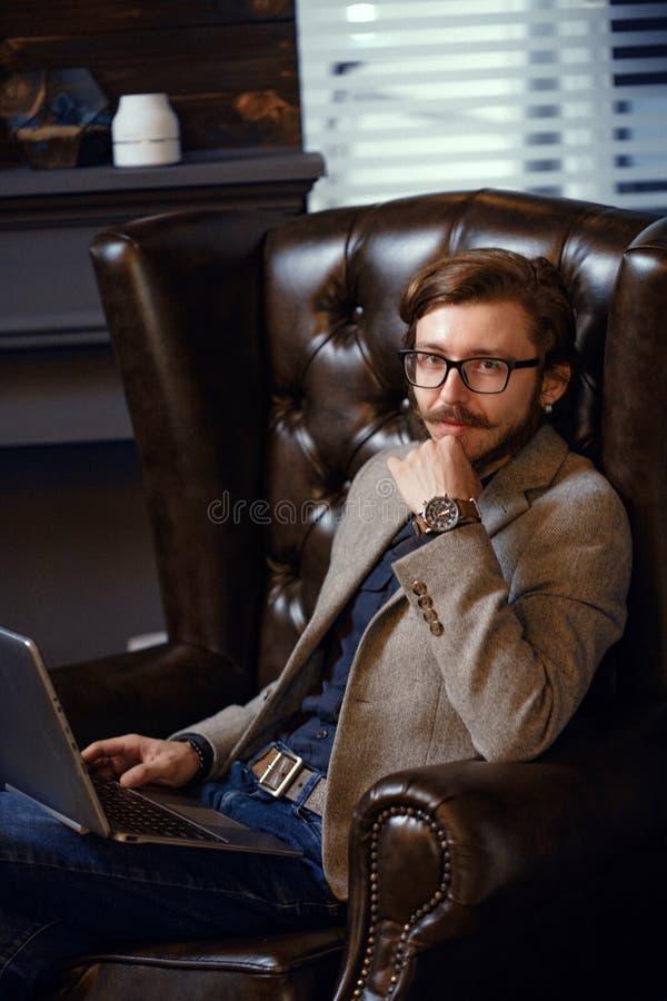 Le den lyckliga unga mannen som sitter i Co-arbete kontorsrum royaltyfri fotografi