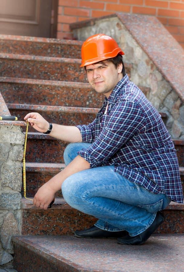 Le den manliga arbetaren som mäter stentrappuppgången med att mäta klappet arkivfoton