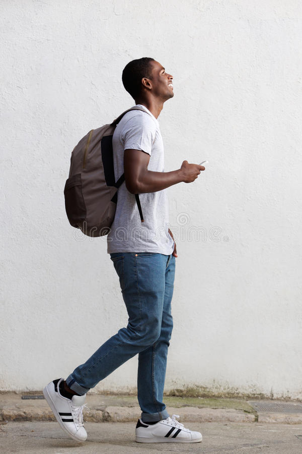 Le den manliga högskolestudenten som går med påsen och mobiltelefonen royaltyfri bild