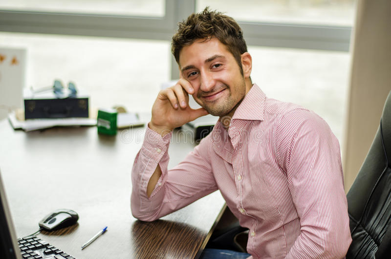 Le den manliga kontorsarbetaren på skrivbordarbete royaltyfri foto
