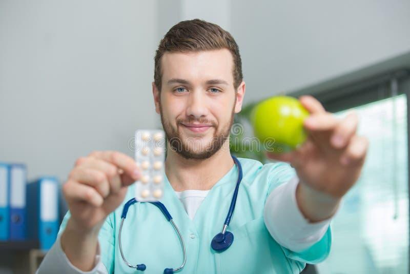 Le den manliga näringsfysiologen med äpplet och preventivpillerar fotografering för bildbyråer