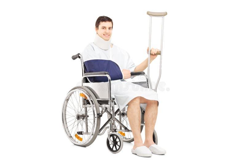 Le den manliga patienten med den brutna armen i en rullstol som rymmer A.C. royaltyfria bilder
