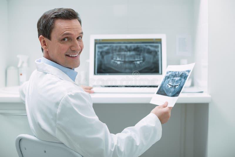 Le den manliga tandläkaren som rymmer en bild arkivbilder