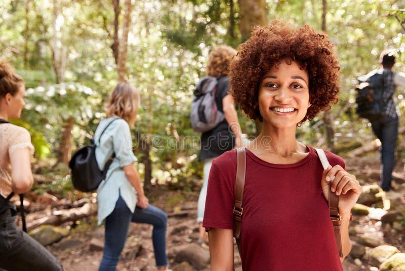 Le den millennial afrikansk amerikankvinnan som fotvandrar i en skog med vänner, midja upp, slut upp royaltyfri fotografi