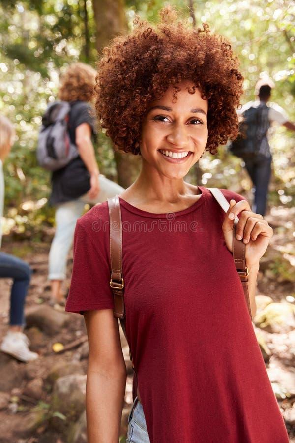 Le den millennial afrikansk amerikankvinnan som fotvandrar i en skog, midja upp, slut upp som är vertikal fotografering för bildbyråer