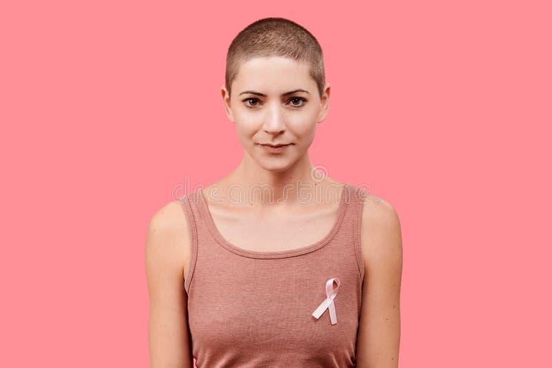 Le den mitt- 30-talkvinnan, en canceröverlevande, bärande rosa bröstcancermedvetenhetband som isoleras över att bo korallbakgrund royaltyfri fotografi