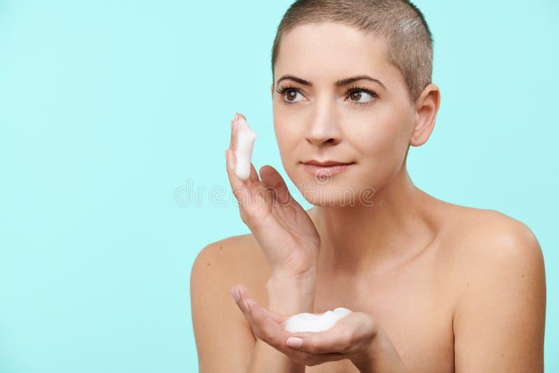 Le den mitt- 30-talkvinnan som använder det ansikts- rengöringsmedlet för försiktigt skum Foto av den attraktiva caucasian kvinna royaltyfri fotografi